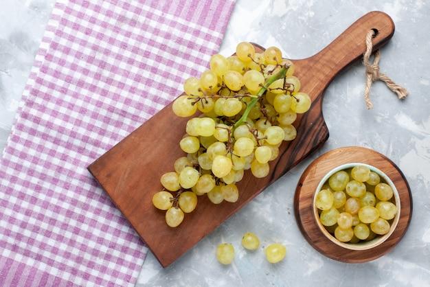 Vista superior de uvas verdes frescas, suculentas e maduras em uma mesa leve, sabor de vitamina de uva