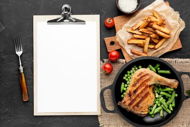 Vista superior de vagens de ervilha e frango assado na panela com batatas e uma prancheta em branco