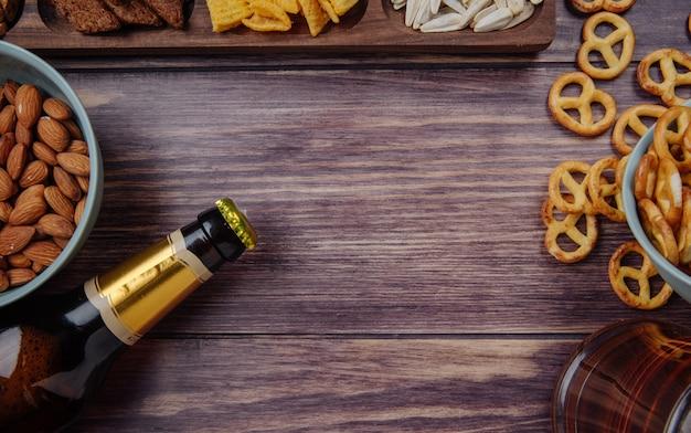 Vista superior de variados lanches de cerveja com uma garrafa de cerveja no rústico, com espaço de cópia