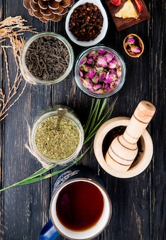 Vista superior de várias especiarias e ervas secas folhas de chá preto, hortelã, botões de rosa, tempero de cravo e pimenta preta em potes de vidro em madeira preta