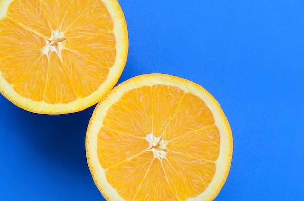 Vista superior de várias fatias de frutas laranja no fundo brilhante na cor azul