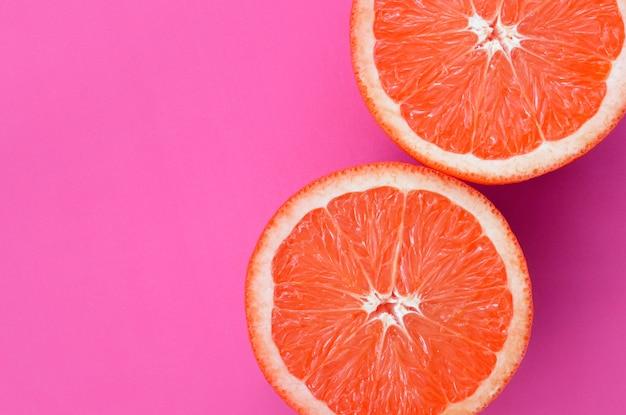 Vista superior de várias fatias de toranja no fundo brilhante na cor roxa