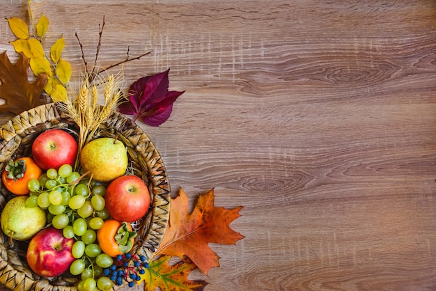 Vista superior de várias frutas coloridas do outono em uma cesta de vime sobre a mesa de madeira. copie o espaço.