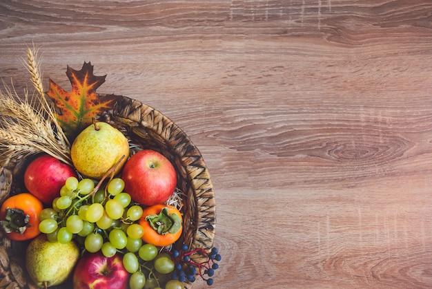 Vista superior de várias frutas coloridas do outono em uma cesta de vime sobre a mesa de madeira.