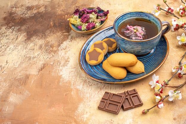 Vista superior de vários biscoitos, uma xícara de chá e barras de chocolate de flores na mesa de cores misturadas