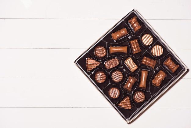 Vista superior de vários bombons de chocolate em caixa com fundo branco de madeira.