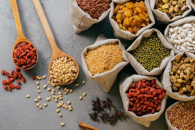 Vista superior de vários grãos e frutos secos coloridos embalados em pequenos sacos de estopa.
