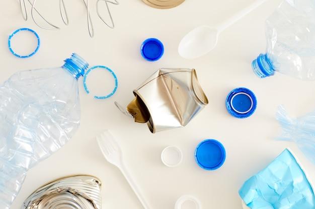 Vista superior de vários itens de lixo dispostos em composição mínima, separação de resíduos e conceito de reciclagem