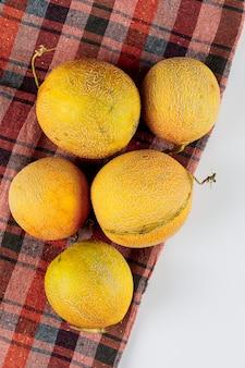 Vista superior de vários melões em um pano de piquenique e fundo branco