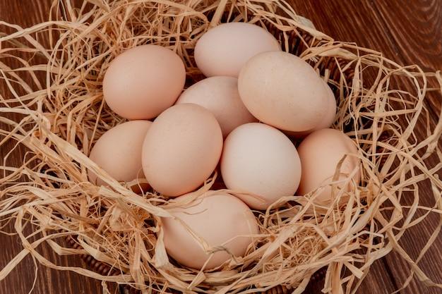 Vista superior de vários ovos de galinha frescos no ninho em fundo de madeira