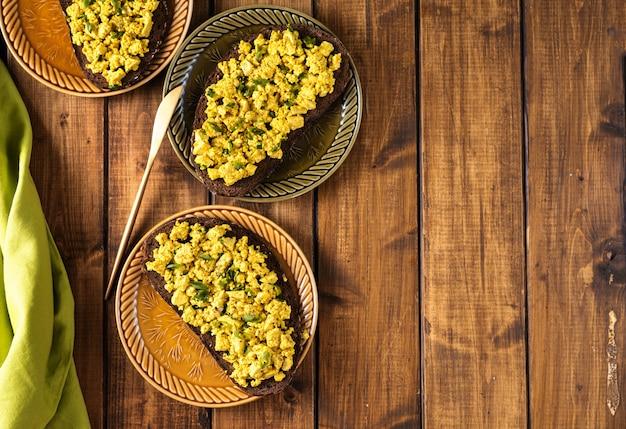 Vista superior de vários pratos com sanduíches de salada de ovo vegan colorido