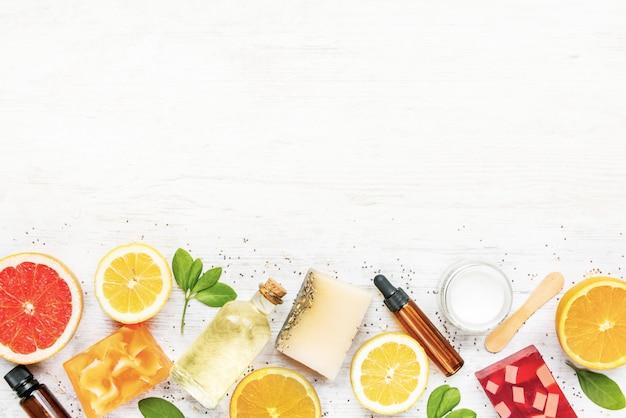 Vista superior de vários sabonetes orgânicos artesanais coloridos, organizados com frutas cítricas, ervas, sementes de chia e aloe.