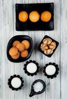 Vista superior de vários tipos de biscoitos doces e muffins em bandejas pretas sobre fundo de madeira