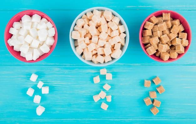 Vista superior de vários tipos de cubos de açúcar em tigelas sobre fundo azul de madeira