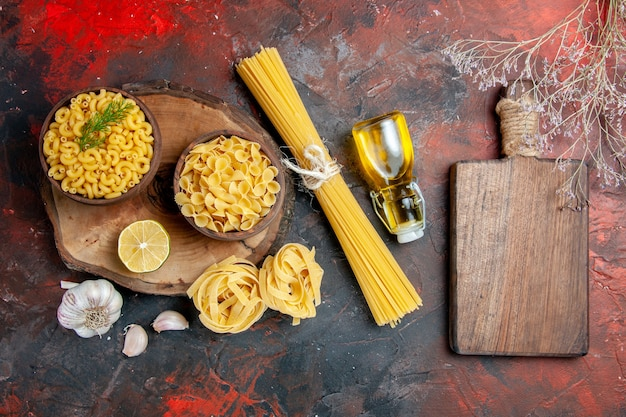 Vista superior de vários tipos de massas crus, alho, limão, óleo, garrafa e tábua de cortar em fundo de cor mista