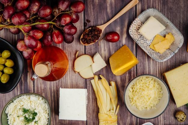 Vista superior de vários tipos de queijo com mel em uma garrafa de vidro e uvas doces em madeira rústica
