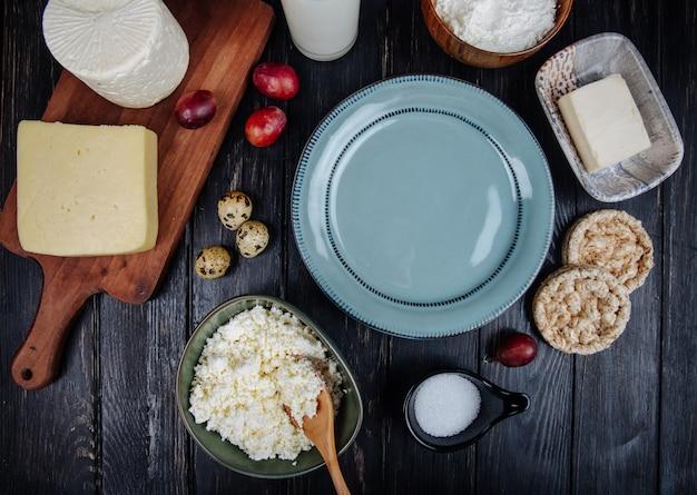 Vista superior de vários tipos de queijo com queijo cottage em uma tigela, ovos de codorna, uvas doces e um prato vazio na mesa de madeira escura