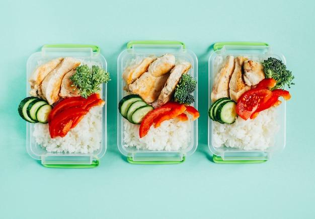 Vista superior de vegetais, arroz e carne em tigelas de plástico sobre fundo verde claro