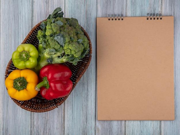 Vista superior de vegetais como brócolis e pimentão em uma cesta com bloco de notas sobre fundo de madeira com espaço de cópia