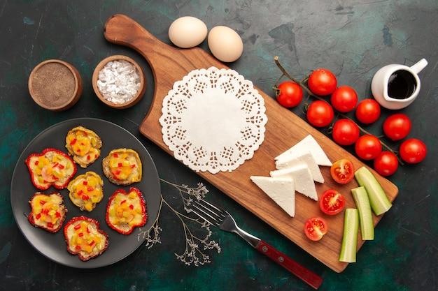 Vista superior de vegetais cozidos com ovos crus e tomates frescos na superfície escura