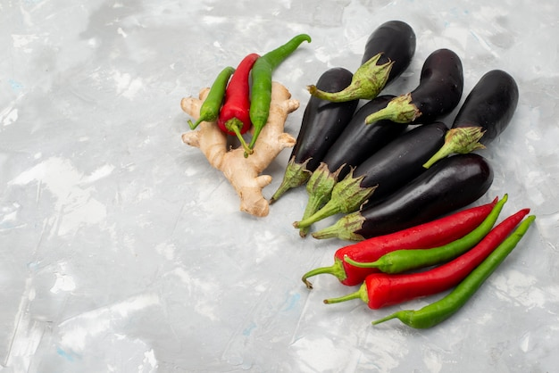 Vista superior de vegetais crus frescos, pimentões e berinjelas na refeição de alimentos vegetais frescos de árvore de fundo claro