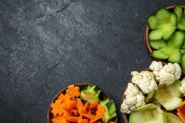 Vista superior de vegetais de design diferente dentro de potes no espaço cinza escuro