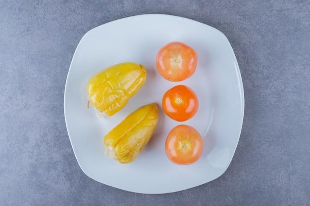 Vista superior de vegetais enlatados. tomate e pimenta no prato branco.
