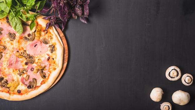 Vista superior de vegetais folhosos; cogumelo e pizza em pano de fundo escuro