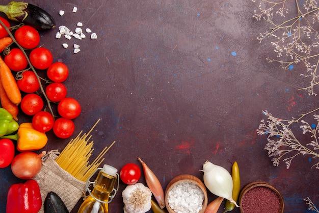 Vista superior de vegetais frescos com massa italiana crua no espaço escuro