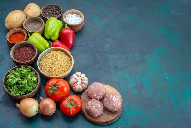 Vista superior de vegetais frescos com temperos de carne e verduras na mesa azul escura