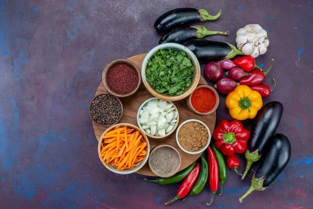 Vista superior de vegetais frescos com temperos e verduras na mesa escura