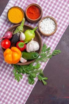 Vista superior de vegetais frescos com temperos em superfície escura, salada madura, comida saudável