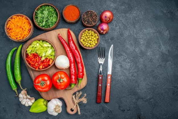Vista superior de vegetais frescos com verduras e feijões em uma mesa escura para salada de vegetais maduros