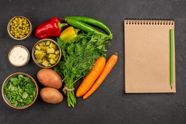 Vista superior de vegetais frescos com verduras na superfície escura