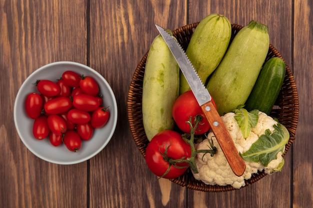 Vista superior de vegetais frescos, como abobrinha, pepino e couve-flor em um balde com faca com tomates em uma tigela sobre um fundo de madeira