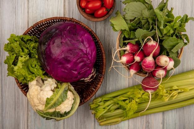 Vista superior de vegetais frescos, como couve-flor, repolho roxo e alface em um balde com rabanetes em um balde com tomates em uma tigela de madeira com aipo isolado em um fundo cinza de madeira