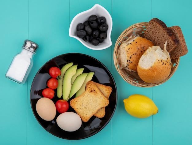 Vista superior de vegetais frescos, como fatias de abacate, tomates, azeitonas, ovos na placa preta com um balde de pães e limão no azul