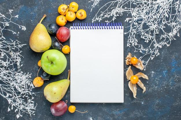 Vista superior de vegetais frescos, como peras, maçã, verde, cerejas, ameixas e um bloco de notas na mesa escura, alimentos com frutas frescas