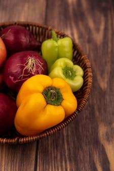 Vista superior de vegetais frescos, como pimentões coloridos e cebolas em um balde em uma superfície de madeira