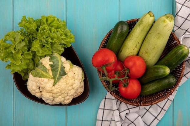 Vista superior de vegetais frescos, como tomates, pepinos e abobrinhas em um balde em um pano xadrez com couve-flor e alface em uma tigela em uma parede de madeira azul