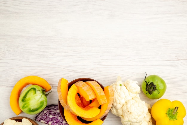 Vista superior de vegetais frescos cortados abóbora em uma tigela verde tomate repolho vermelho pimentão couve-flor na superfície de madeira branca com espaço livre