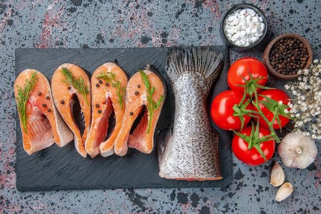 Vista superior de vegetais frescos de peixes crus na bandeja de cor escura tempera tomates com hastes de alho e flores na tabela de cores de mistura de preto azul