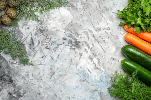 Vista superior de vegetais frescos em galho de pinheiro de placa oval em fundo escuro