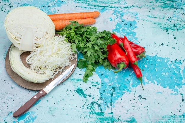 Vista superior de vegetais frescos fatiados de vegetais, repolho, cenoura e pimentão em azul-claro