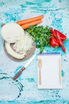 Vista superior de vegetais frescos fatiados de vegetais, repolho, cenouras e pimentões com bloco de notas em azul-claro