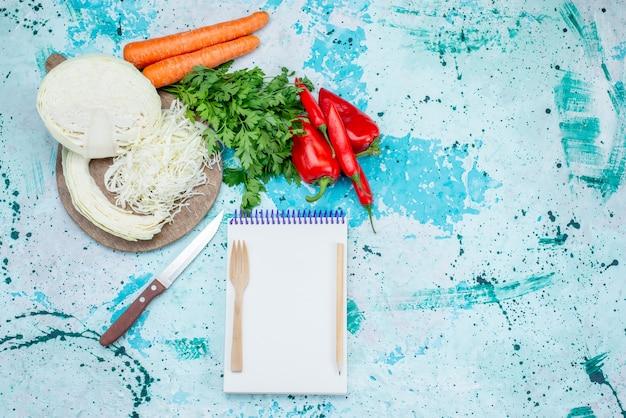 Vista superior de vegetais frescos fatiados de verduras, repolho, cenoura e pimentão com bloco de notas em azul-claro