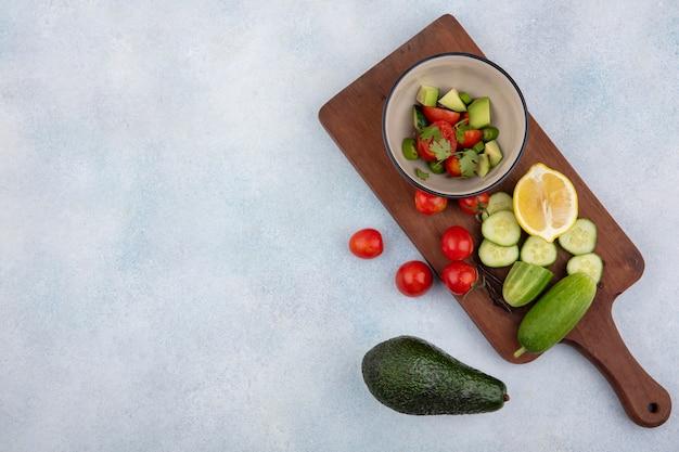 Vista superior de vegetais frescos, incluindo pepino e tomate em uma tigela na mesa de madeira da cozinha com fatias de pepino picado, tomate cereja limão e abacate no branco