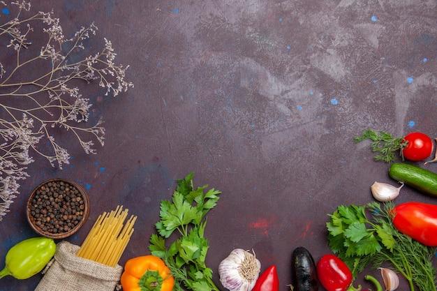 Vista superior de vegetais frescos maduros com verduras na superfície escura de salada de vegetais de cor madura