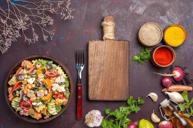 Vista superior de vegetais frescos. salada com temperos diferentes no preto