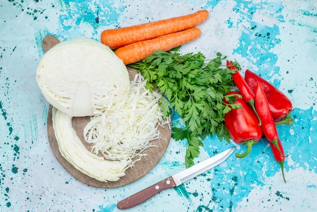Vista superior de vegetais frescos, vegetais fatiados, repolho, cenoura e pimenta picante em azul-claro, refeição de comida com vegetais, salada saudável